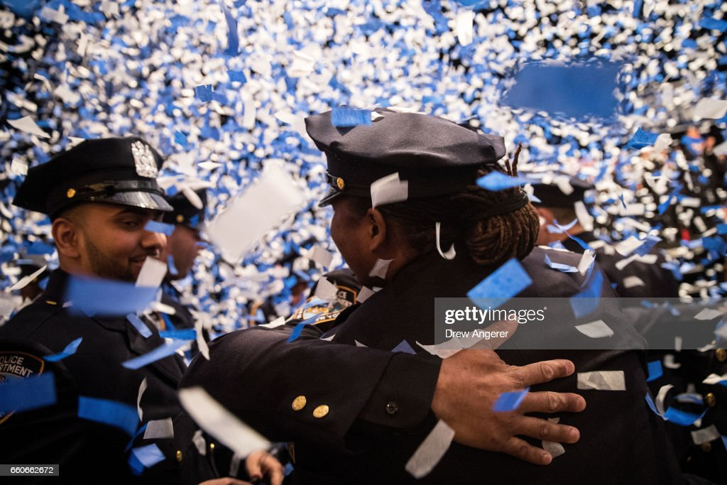 The newest members of the New York City Police Department (NYPD) embrace at the conclusion of their police academy graduation ceremony at the Theater at Madison Square Garden, March 30, 2017 in New York City. Over 600 new officers were sworn in during the ceremony.