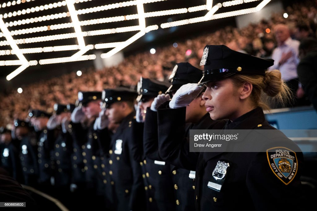 The newest members of the New York City Police Department (NYPD) salute during their police academy graduation ceremony at the Theater at Madison Square Garden, March 30, 2017 in New York City. Over 600 new officers were sworn in during the ceremony.