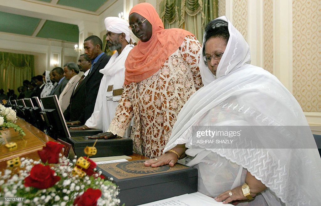 The newly appointed Sudanese ministers place their hands on the koran as they are sworn in on June 16, 2010, in Khartoum. The new government, consisting of 24 members of the president's National Congress Party, eight members of the former southern rebel Sudan People's Liberation Movement and three small parties, must tread carefully to reach the key referendum on independence for south Sudan scheduled for January.