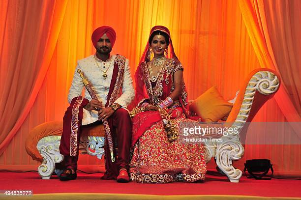 The newly wedded couple Indian cricketer Harbhajan Singh and Geeta Basra posing for lensmen after getting married on October 29 2015 at a resort on...