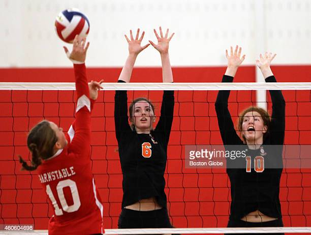 The Newton North Tigers' Tess Simmons left and Kristen Copley right go for the block on the Barnstable Red Raiders' Emma Glover Barnstable High...
