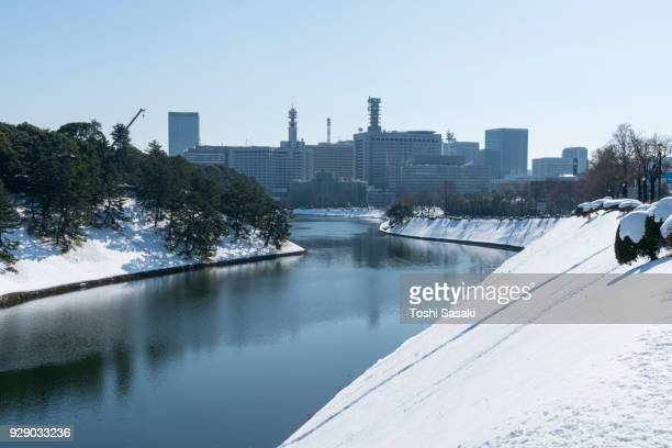 The next morning of winter snowstorm at Chiyoda-ku Tokyo Japan – January. 23 2018. Kasumigaseki district and Hibiya district high-rise buildings stand behind the snowy Imperial Palace Moat, which are reflecting to the water surface of the moat.