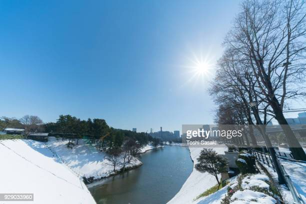 The next morning of winter snowstorm at Chiyoda-ku Tokyo Japan – January. 23 2018. Kasumigaseki district and Nagatacho district high-rise buildings stand behind the snowy Imperial Palace Moat, which are reflecting to the water surface of the moat.