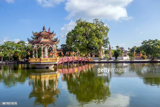 The Ngoi tile-roofed Bridge cross Hoanh river,in centre of Hai Anh town,Vietnam, old covered wooden bridge with tiled roof color red
