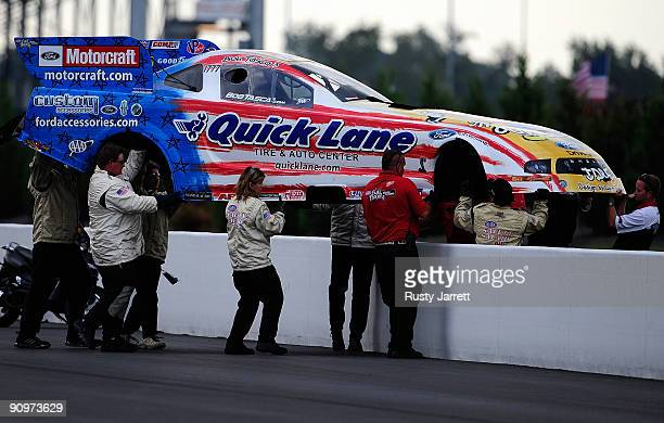 The NHRA Safety Safari carries the body from Bob Tasca's funny car over the wall during qualifying for the NHRA Carolinas Nationals on September 19...