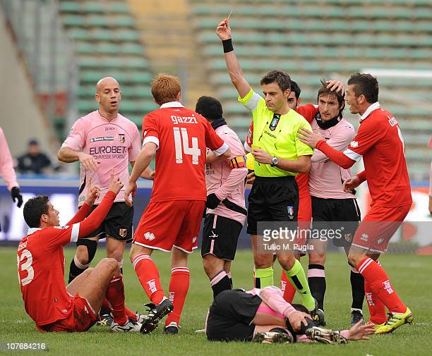 The Nicola Rizzoli gets a red card to Marco Rossi of Bari as Antonio Nocerino looks injured during the Serie A match between Bari and Palermo at...