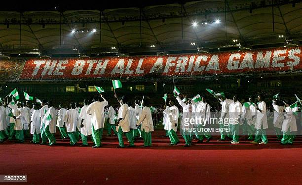 The Nigerian contingent for the 8th All Africa Games march past a display on the terrace of Abuja stadium 04 October 2004 at the opening ceremony in...