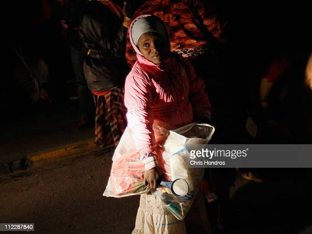 The Nigerian daughter of migrant worker waits with a bag to board a relief ship to leave the besieged city of Misrata April 17 2011 at the port in...