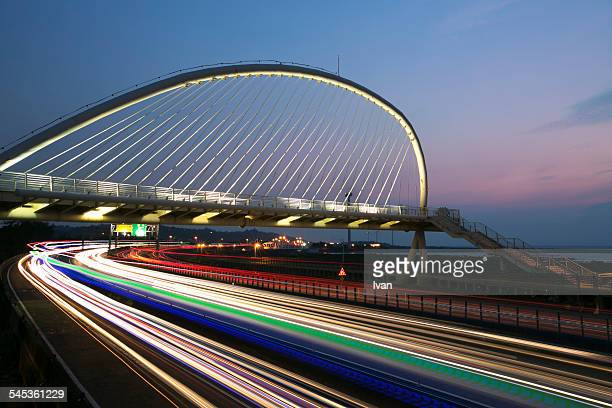 The night view of harp bridge with car trace