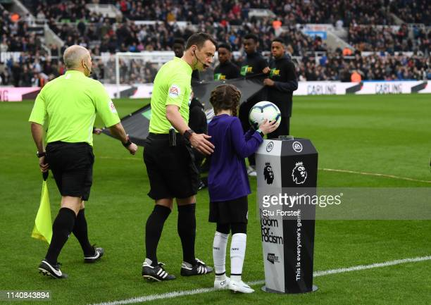 The Nike match ball is picked up off the 'No Room for Racism' plinth by the mascot as referee Stuart Atwell looks on before the Premier League match...
