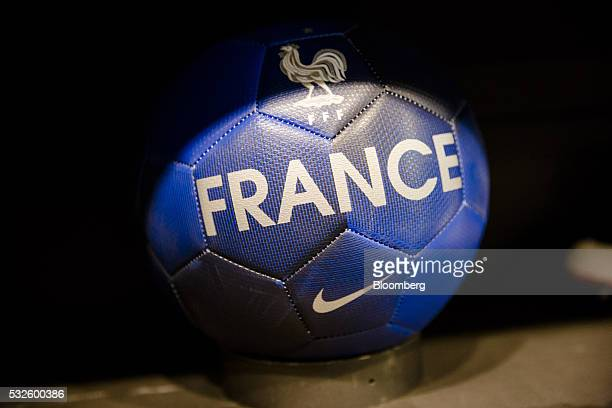 The Nike Swoosh and a French Football Federation Gallic rooster logo sit on a football inside the Nike Inc sports apparel store in Paris France on...