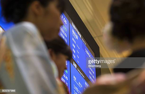 The Nikkei 225 Stock Average figure is displayed on a monitor as women wearing kimonos stands during a ceremony marking the first trading day of the...