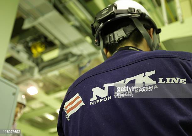 The Nippon Yusen KK logo is seen on an uniform of an employee during a media tour for the company's car transporter ship Auriga Leader at Mitsubishi...