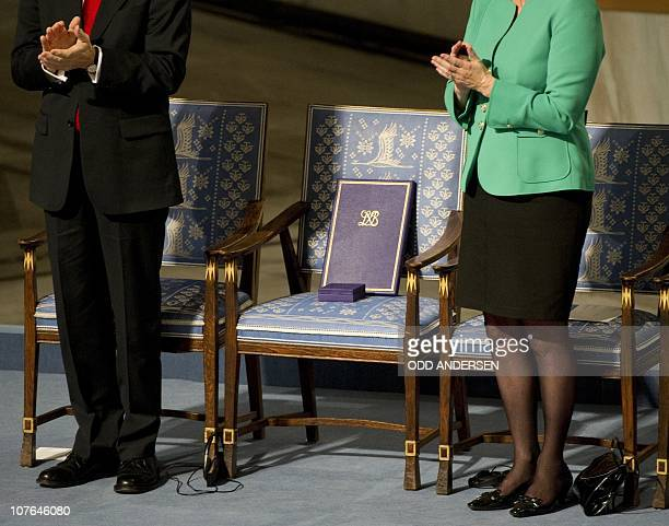The Nobel Peace Prize committee Chairman Thorbjoern Jagland and Kaci Kullmann Five applaud as they stand next to the empty chair of the laureate...