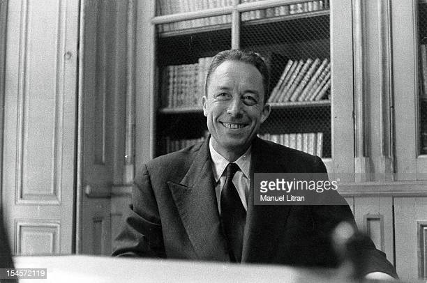 The Nobel Prize in literature has been attributed to Albert Camus plan smiling face of the writer sitting at a table