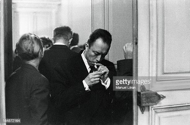 The Nobel Prize in literature has been attributed to Albert Camus the writer lighting a cigarette between two doors