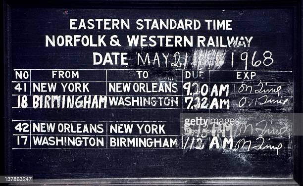 The Norfolk Western Railway chalkboard schedule of arriving trains affixed to the outside of the small passenger depot in Abingdon Virginia shows...