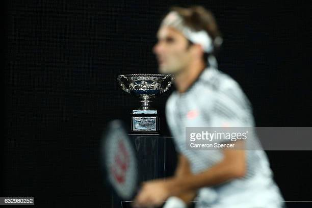 The Norman Brookes Challenge Cup is seen as Roger Federer of Switzerland prepares to return a shot in his Men's Singles Final match against Rafael...