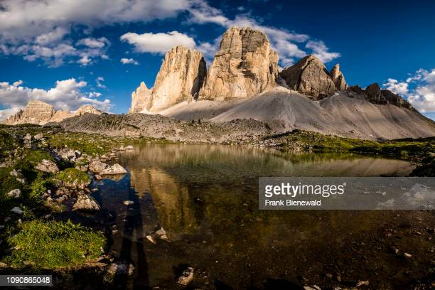 The north faces of the mountain group Tre Cime di Lavaredo mirroring in a lake.