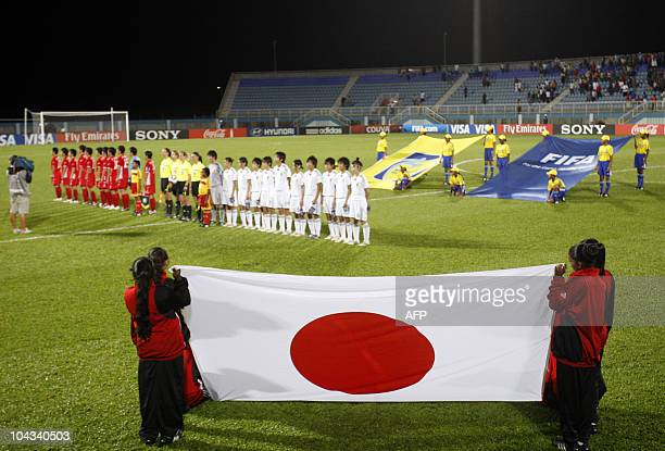 The North Korean and Japanese teams players stand in the field before the FIFA Women's Under17 semifinal match on September 21 at the Ato Boldon...
