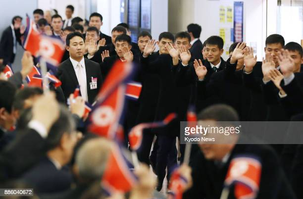 The North Korean men's national soccer side are greeted by compatriots upon arriving at Tokyo's Haneda airport on Dec 5 for the E1 Football...