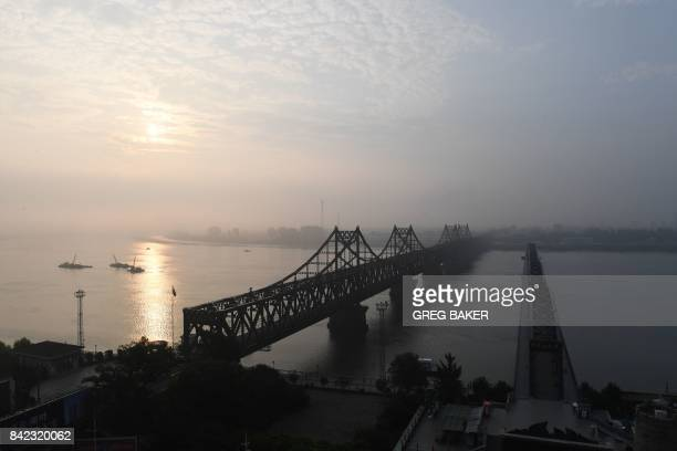 TOPSHOT The North Korean town of Sinuiju is seen behind the Friendship Bridge which connects Sinuiju and the the Chinese border city of Dandong and...