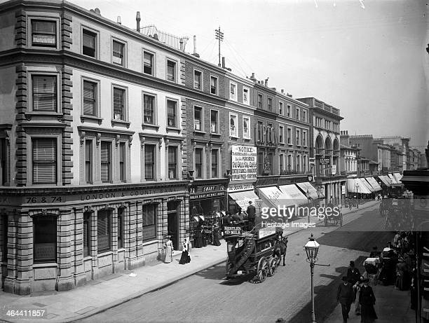 The north side of Westbourne Grove, Paddington, London, c1895. A horse drawn omnibus drives along a prosperous shopping street. A row of shops have...