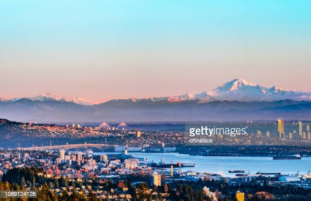 the north vancouver skyline and ships in the harbour and snow mountains visible in the background - vancouver canada stock pictures, royalty-free photos & images