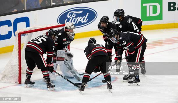 The Northeastern Huskies huddle around Cayden Primeau before a game against the Boston College Eagles during NCAA hockey in the championship game of...