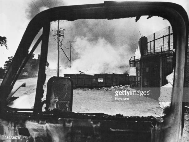 The Norton Tire Company ablaze, pictured through the window of a burnt-out truck, during the riots in Miami, Florida, July 1980. The violence...