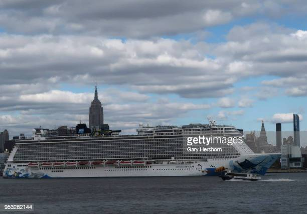 The Norwegian Escape cruise ship sails in the Hudson River next to a NY Waterway ferry as it passes the Empire State Buidling in New York City on...