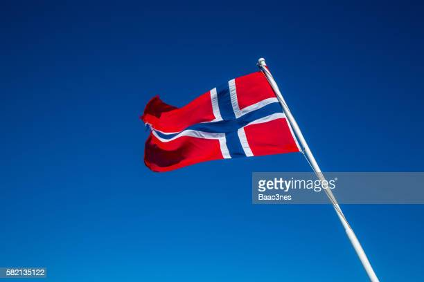 the norwegian flag with blue sky in the background - norwegian flag stock pictures, royalty-free photos & images