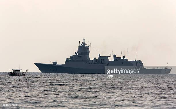 The Norwegian frigate Helge Ingstad sails past a fishing boat as it leaves the port of Limassol in the east Mediterranean island of Cyprus for waters...