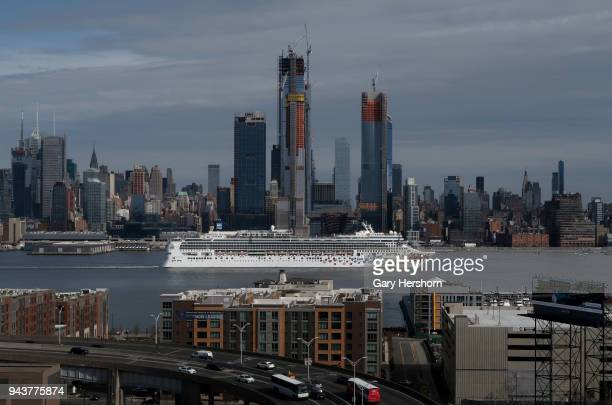 The Norwegian Gem cruise ship sails in the Hudson River past the skyline of New York City as cars enter and exit the Lincoln Tunnel in New Jersey on...