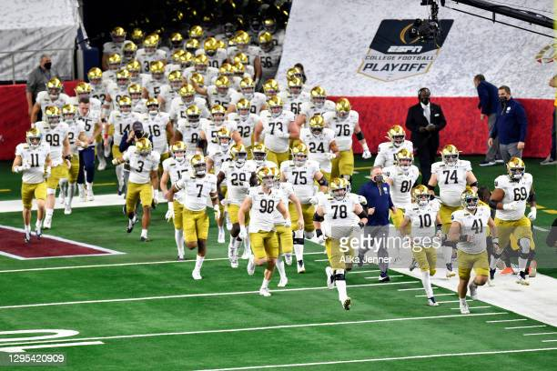 The Notre Dame Fighting Irish run on the field during player introductions before the College Football Playoff Semifinal at the Rose Bowl football...
