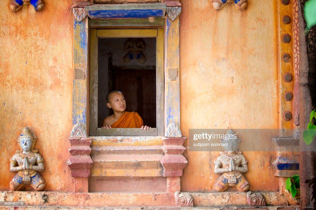 The novice stands looking at the rectangular frame of the window. : Stock-Foto