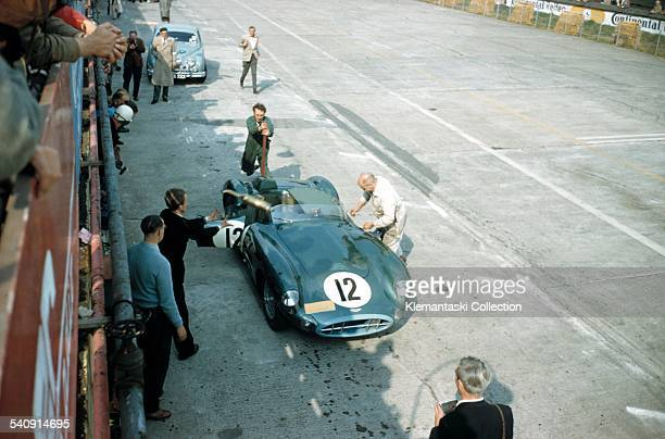 The Nürburgring 1000km Race Nürburgring May 26 1957 Aston mechanic Eric Hind rushes to jack up the rear end of the Aston Martin as they practice a...