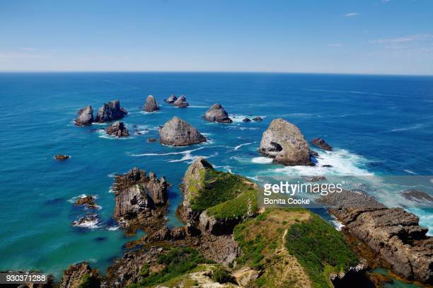 the nuggets, rocks near the shore at nugget point lighthouse, in the catlins - region otago stock-fotos und bilder