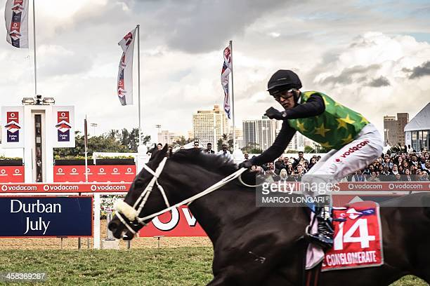 The number 14 jockey gestures on his horse The Conglomerate as he wins at the Greyville Race Course during the annual Durban July horse race in...