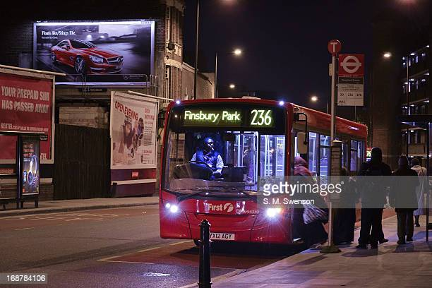CONTENT] The number 236 bus to Finsbury Park in Hackney East London It is night in an urban setting with the bus lit up and a good view of the driver...