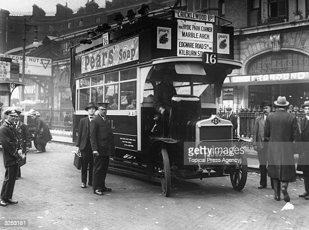 The number sixteen motor bus to Cricklewood at a central London bus stop There is an advertisement for Pear's Soap on its side