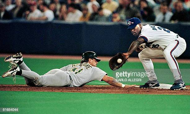 The Oakland A's lead off hitter Damon Mashore dives back safely to first as the Toronto Blue Jay's first baseman Carlos Delgado catches the ball at...
