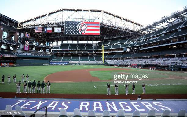 The Oakland Athletics and the Texas Rangers stand for a moment of silence in remembrance of 9/11 at Globe Life Field on September 11 2020 in...