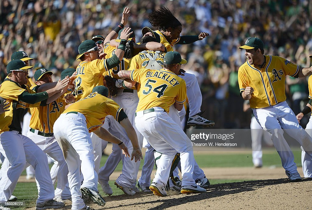 The Oakland Athletics celebrate on the mound after defeating the Texas Rangers 12-5 to capture the American League West title at O.co Coliseum on October 3, 2012 in Oakland, California.
