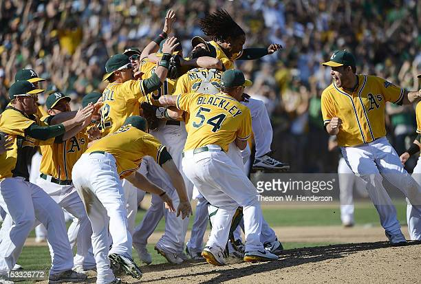The Oakland Athletics celebrate on the mound after defeating the Texas Rangers 125 to capture the American League West title at Oco Coliseum on...