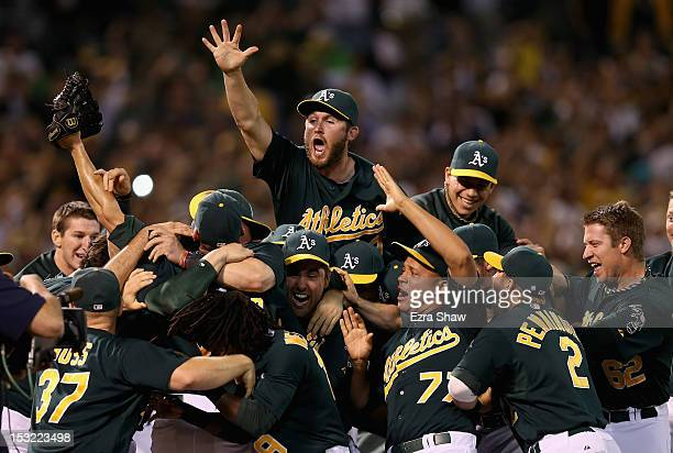 The Oakland Athletics celebrates after the Athletics beat the Texas Rangers to clinch a playoff spot at Oco Coliseum on October 1 2012 in Oakland...
