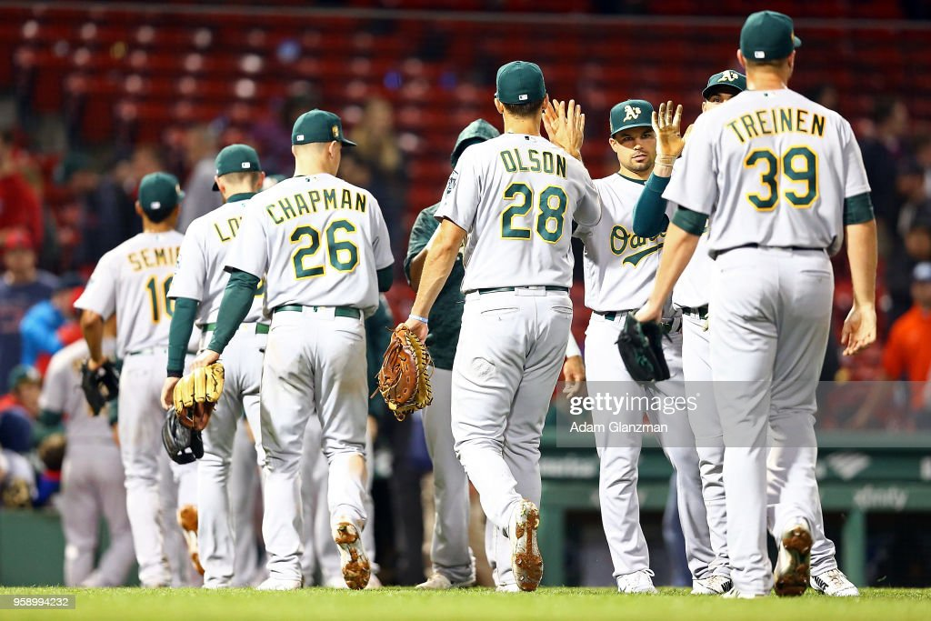 The Oakland Athletics high five each other after a victory over the Boston Red Sox at Fenway Park on May 15, 2018 in Boston, Massachusetts.