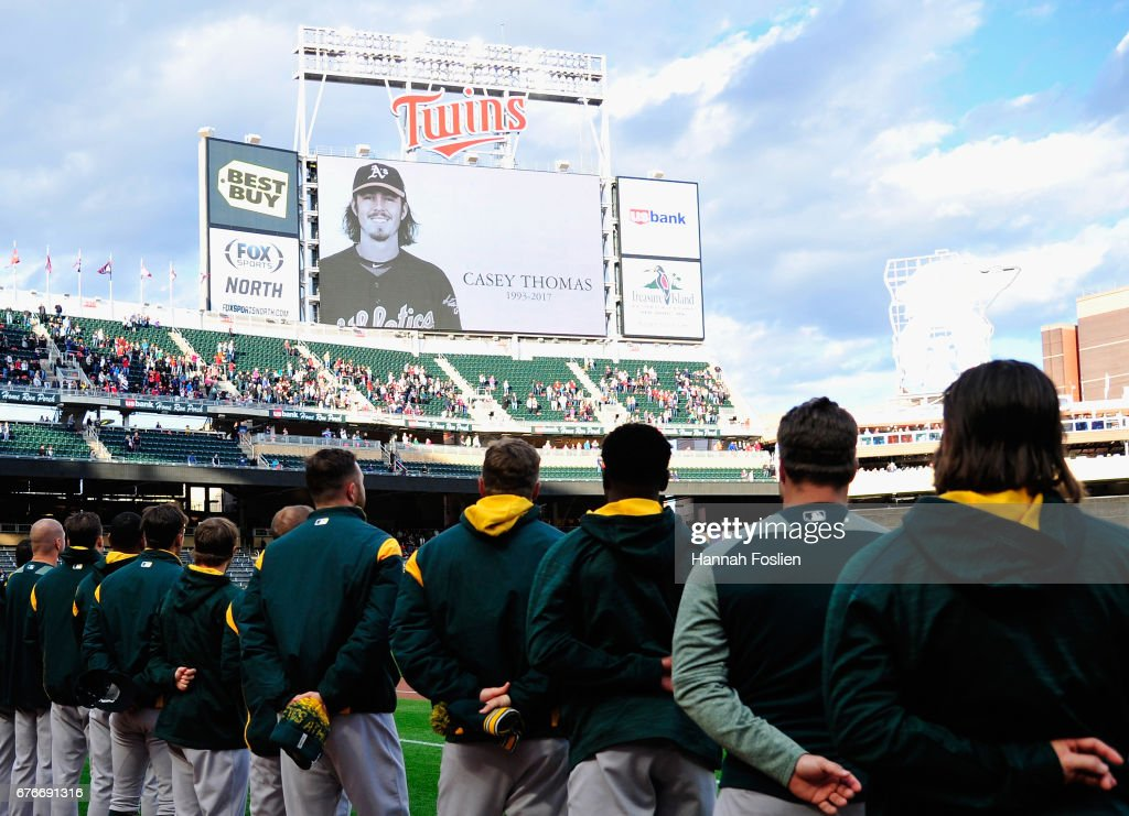 The Oakland Athletics stand for a moment of silence for minor league player Casey Thomas, who died suddenly today, before a game against the Minnesota Twins on May 2, 2017 at Target Field in Minneapolis, Minnesota.