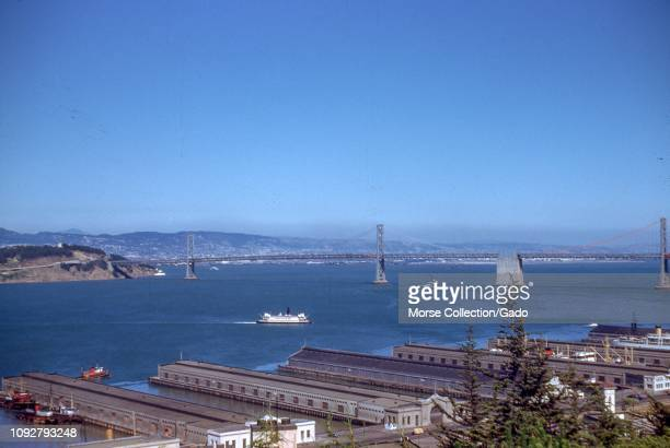 The Oakland San Francisco Bay Bridge San Francisco Bay piers Embarcadero neighborhood and a ferry boat are visible in an aerial view of San Francisco...