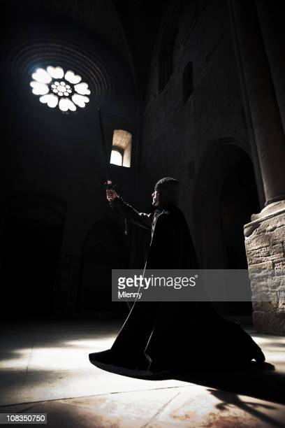 the oath kneeling knight raising sword praying into cathedral light. - excalibur stock photos and pictures